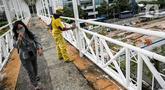 Warga melintasi pekerja Dinas Bina Marga DKI yang mengecat ulang tiang Jembatan Penyeberangan Orang (JPO) di kawasan Thamrin, Jakarta, Kamis (28/1/2021). Pengecatan ulang itu sebagai bagian dari perawatan JPO di Jakarta guna memberikan kesan bersih dan indah. (Liputan6.com/Faizal Fanani)