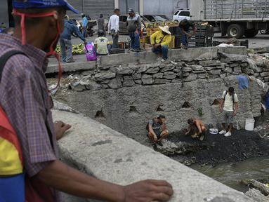 Pria mencari potongan tembaga, emas atau perak untuk dijual di tengah pandemi virus corona baru di Sungai Guaire yang tercemar, di lingkungan Quinta Crespo di Caracas, Venezuela (19/1/2021). Krisis ekonomi Venezuela telah mengirim jutaan orang melarikan diri. (AP Photo/Matias Delacroix)