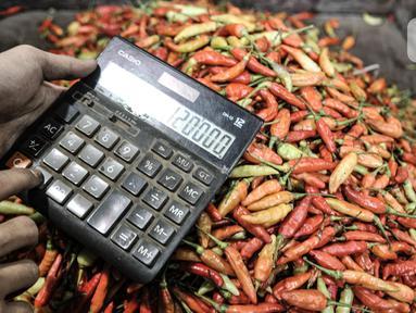 Pedagang menghitung harga cabai rawit merah yang dipesan pembeli menggunakan kalkulator di Pasar Senen, Jakarta, Kamis (4/3/2021). Data Ikatan Pedagang Pasar Indonesia (Ikappi) mencatat harga cabai rawit merah saat ini di pasaran berkisar Rp120.000 per kilogram. (merdeka.com/Iqbal S. Nugroho)