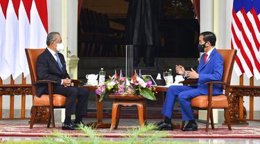 Presiden Indonesia Joko Widodo (kanan) berbincang dengan Perdana Menteri Malaysia Muhyiddin Yassin saat bertemu di Istana Merdeka, Jakarta, Jumat (5/2/2021). Baik Jokowi maupun Muhyiddin Yasin terlihat sama-sama mengenakan masker. (Agus Suparto, Indonesian President Palace via AP)