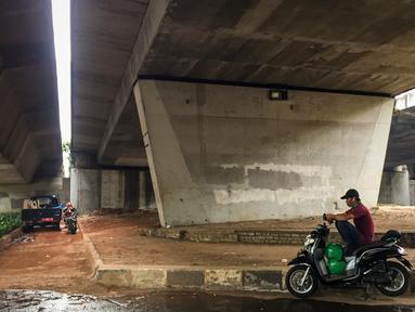 Pengendara motor beristirahat di jalur putar balik Jalan Gatot Soebroto, kawasan Kuningan, Jakarta, Selasa (12/11/2019). Jalur yang kini hanya bisa dilalui kendaraan roda dua itu menjadi lokasi sebagian pemotor beristirahat karena teduh tertutup jalan tol dalam kota. (Liputan6.com/Immanuel Antonius)