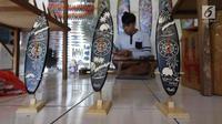 Pengrajin membuat sovenir papan seluncur di Bali, Senin (15/10). KUR yang disediakan pemerintah untuk sektor pariwisata sebagai upaya pengembangan destinasi di Indonesia. (Liputan6.com/Angga Yuniar)