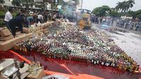 Sebuah alat berat melindas ribuan botol miras ilegal hasil sitaan di Kantor Pusat Bea Cukai, Jakarta, Senin (20/6). Bea dan Cukai melakukan pemusnahan terhadap berbagai hasil temuan senilai Rp46,1 miliar. (Liputan6.com/Immanuel Antonius)