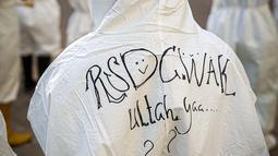 Tenaga kesehatan menuliskan ucapan setahun RSDC Wisma Atlet saat acara bermain angklung di RSDC Wisma Atlet, Kemayoran, Jakarta, Selasa (23/3/2021). Acara tersebut dilakukan dalam rangka satu tahun beroperasinya RSDC Wisma Atlet Kemayoran. (Liputan6.com/Faizal Fanani)