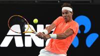 Petenis Spanyol, Rafael Nadal mengembalikan bola ke arah petenis Austria, Dominic Thiem dalam pertandingan tenis eksibisi di Adelaide, Jumat (29/1/2021) menjelang berlangsungnya Turnamen Tenis Australia Open. Rafael Nadal menang 7-6, 6-4 atas Dominic Thiem. (AFP/Michael Errey)