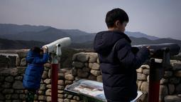 Dua anak laki-laki melihat teropong di atap vila yang dikenal sebagai Kastil Hwajinpo di Pantai Hwajinpo, Korea Selatan, (19/2). Villa ini termasuk dalam wilayah Korea Utara sebelum perang tahun 1950- 53. (AP Photo/Jae C. Hong)