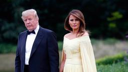 Presiden AS Donald Trump dan Melania Trump meninggalkan Winfield House di London, Kamis (12/7). Menghadiri acara makan malam, Melania terlihat begitu cantik dan anggun dalam balutan gaun panjang dengan 'cape' warna kuning. (AP/Pablo Martinez Monsivais)