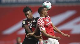 Striker Bayern Munich, Kingsley Coman (kiri) berduel udara dengan striker FSV Mainz, Robin Quaison dalam laga lanjutan Liga Jerman 2020/2021 pekan ke-31 di Opel Arena, Mainz, Sabtu (24/4/2021). Bayern Munich kalah 1-2 dari FSV Mainz. (AP/dpa)