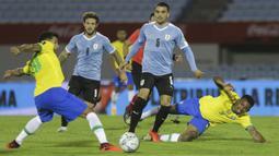 Penyerang Brasil, Roberto Firmino, berebut bola dengan gelandang Uruguay, Nahitan Nandez, pada laga lanjutan kualifikasi Piala Dunia zona CONMEBOL di Estadio Centenario, Rabu (18/11/2020) pagi WIB. Brasil menang 2-0 atas Uruguay. (AFP/Matilde Campodonico/pool)