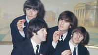 Personil The Beatles George Harrison, Paul McCartney, John Lennon dan Ringo Starr menunjukkan medali yang diberikan Ratu Elizabeth II dalam sebuah upacara di Istana Buckingham di London, Inggris pada 26 Oktober 1965. (AP Photo, File)