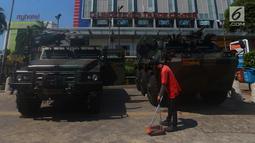Petugas kebersihan menyapu di depan kendaraan lapis baja TNI di pertokoan Glodok, Jakarta, Jumat (11/5). Pengamanan ketat dilakukan guna antisipasi peristiwa yang tidak diinginkan terkait Aksi Bela Palestina di Monas. (Merdeka.com/Imam Buhori)