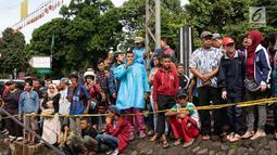 Warga melihat proses evakuasi KRL yang anjlok di kawasan Kebon Pedes, Bogor, Jawa Barat, Minggu (10/3). Kepala Daop I Jakarta Dadan Risdiansyah memastikan penanganan KRL yang anjlok selesai hari ini. (Liputan6.com/Immanuel Antonius)