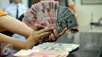 Petugas memperlihatkan uang pecahan US$100 dan rupiah di pusat penukaran uang, Jakarta, , Rabu (12/8/2015). Reshuffle kabinet pemerintahan Jokowi-JK, nilai Rupiah terahadap Dollar AS hingga siang ini menembus Rp 13.849. (Liputan6.com/Johan Tallo)