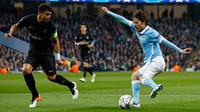 Gelandang Manchester City, David Silva (kanan) berusaha melewati bek PSG, Thiago Silva di leg kedua liga Champions di Etihad Stadium, Inggris (13/4). City menang atas PSG dengan skor 1-0. (Reuters/Jason Cairnduff)