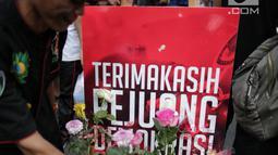 Pengunjung car free day meletakan bunga yang diberikan oleh anggota TKN Milenial Jokowi-Ma'ruf dalam kegiatan tabur bunga di Bundaran HI, Jakarta, Minggu (28/4/2019). Aksi tersebut sebagai bentuk duka atas meninggalnya 272 petugas KPPS dalam Pemilu 2019. (Liputan6.com/Faizal Fanani)