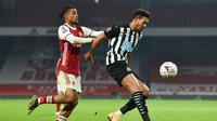 Striker Newcastle United, Joelinton (kanan) menguasai bola dibawah tekanan gelandang Arsenal, Reiss Nelson dalam laga babak ke-3 Piala FA 2020/21 di Emirates Stadium, Sabtu (9/1/2021). Newcastle United kalah 0-2 dari Arsenal melalui extra time. (AFP/Glyn Kirk/Pool)