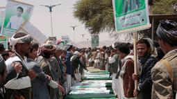 Warga Yaman menghadiri pemakaman puluhan bocah korban serangan koalisi Arab Saudi, di Saada, Senin (13/8). Warga membawa foto korban sementara pejuang Houthi mengatur mereka agar pemakaman berjalan aman. (AP/Hani Mohammed)