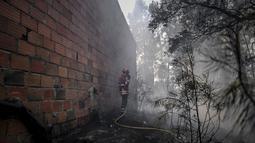 Seorang petugas pemadam kebakaran berdiri di sebelah sebuah rumah setelah kebakaran hebat di Sarnadas, Macao, di Portugal tengah (21/7/2019). Puluhan orang tewas akibat  kebakaran hutan tersebut. (AFP Photo/Patricia De Melo Moreira)