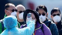 Petugas memeriksa suhu tubuh penumpang asing yang turun dari kapal pesiar Diamond Princess yang dikarantina di Yokohama, Jepang, Jumat (21/2/2020). Sebanyak 74 WNI berada dalam kapal pesiar Diamond Princess, empat di antaranya positif terjangkit virus corona (COVID-19). (AP Photo/Eugene Hoshiko)