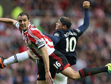 Wayne Rooney duel udara dengan J. O'Shea pada pertandingan sepak bola Liga Inggris antara Sunderland dan Manchester United di Stadion of Light di Sunderland (05/10/13). (AFP/Ian MacNicol)