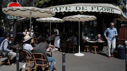 Orang-orang duduk di teras Cafe de Flore di Paris, Selasa (2/6/2020). Warga Paris terkurung selama berbulan-bulan karena lockdown Corona namun, kini sebagian kafe dan restoran di kota itu dibuka kembali usai pelonggaran pembatasan. (AP Photo/Christophe Ena)