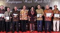 Menteri Keuangan Sri Mulyani (empat kanan) foto bersama dengan President Commissioner EMTEK Eddy Kusnadi Sariaatmadja (tiga kanan) usai memberikan apresiasi dan penghargaan di Kantor Pajak Kanwil DJP Jakarta, Rabu (13/3). (Liputan6.com/JohanTallo)