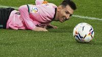 Megabitang Barcelona, Lionel Messi berbaring di lapangan saat menghadapi Valladolid pada laga pekan ke-15 Liga Spanyol di Stadion Jose Zorrilla, Selasa (22/12/2020). Lionel Messi resmi melewati rekor Pele saat membantu Barcelona menggulung Valladolid 3-0 dalam laga tersebut. (Cesar Manso/Pool via AP