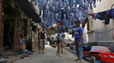 Anak-anak bermain bola di sebuah gang dengan jeans tergantung untuk dijual di pasar pakaian bekas di Kolkata, India, 10 Maret 2016. Kota ini memiliki kekurangan perumahan yang parah, setidaknya 1 juta orang tidur di jalan. (REUTERS/Rupak De Chowdhuri)