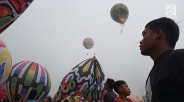 Seorang pria melihat balon udara dinaikan di Lapangan Pagerejo, Kertek, Kabupaten Wonosobo,  Sabtu (15/6/2019). Festival ini untuk memeriahkan syawalan dan wujud syukur warga yang hidup di lereng gunung sindoro dan sumbing. (Liputan6.com/Gholib)