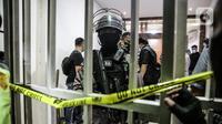 Polisi berjaga saat penggeledahan di lokasi bekas Sekretariat Markas Front Pembela Islam di Petamburan, Jakarta, Selasa (27/4/2021). Munarman juga diduga menyembunyikan informasi tentang tindak pidana terorisme. (Liputan6.com/Faizal Fanani)