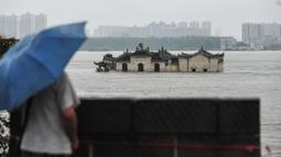 Warga memandangi kuil Guanyinge berumur 700 tahun yang dibangun di atas batu, terendam banjir akibat meluapnya sungai Yangtze di Wuhan, provinsi Hubei pada 19 Juli 2020. Hujan lebat sejak bulan Juni telah menyebabkan sedikitnya 141 orang tewas dan memaksa hampir 15 juta orang dievakuasi. (STR/AFP)