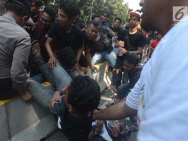 Dua orang pria terjatuh saat terjadi aksi saling dorong antara polisi dan massa driver taksi online yang tergabung dalam Aliando di Jalan Medan Merdeka Barat, Jakarta, Rabu (28/3). (Merdeka.com/Imam Buhori)