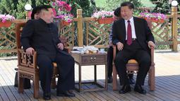 Pemimpin Korea Utara Kim Jong-un berbincang dengan Presiden China Xi Jinping pada pertemuan mereka di Dalian, Selasa (8/5). Kedua pemimpin negara bertemu selama dua hari di awal pekan ini. (Korean Central News Agency/Korea News Service via AP)