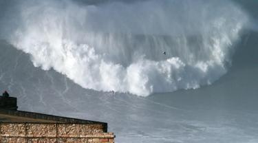 Peselancar asal Australia Ross Clarke-Jones saat menaklukan ombak selama sesi surfing ombak besar di Praia do Norte, atau pantai utara, di Nazare, Portugal, (18/1). (AP Photo / Armando Franca)