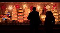 Wisawatan mengunjungi stand yang ada di pasar Natal di luar City Hall, Wina pada 26 November 2018. Christkindlmarkt menjadi ciri khas Natal dan musim dingin di Austria dan juga Jerman yang sudah sejak pertengahan tahun 1310. (JOE KLAMAR / AFP)