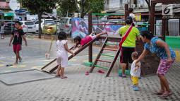 Anak-anak bermain perosotan di Ruang Publik Terbuka Ramah Anak (RPTRA) Rusun Petamburan, Jakarta, Selasa (9/10). Pemprov DKI Jakarta memangkas anggaran pembangunan RPTRA. (Liputan6.com/Faizal Fanani)