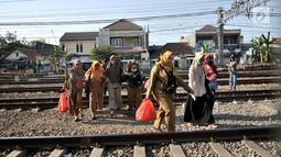 Ibu-ibu menyeberangi perlintasan rel kereta api di kawasan Pisangan Baru, Jakarta, Selasa (10/9/2019). Mereka nekat menantang maut menyeberangi rel di dekat stasiun Jatinegara tersebut lantaran tidak adanya akses jembatan penyeberangan orang (JPO). (merdeka.com/Iqbal Nugroho)