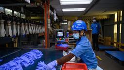 Seorang pekerja memeriksa sarung tangan sekali pakai di pabrik Top Glove di Shah Alam di pinggiran Kuala Lumpur (26/8/2020). Top Glove, sebuah perusahaan yang berbasis di Malaysia adalah salah satu produsen sarung tangan karet terbesar di dunia. (AFP/Mohd Rasfan)