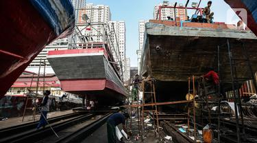Aktivitas pekerja saat memperbaiki kapal di sebuah galangan kapal kawasan Muara Angke, Jakarta Utara, Kamis (3/6/2021). Banyaknya aktivitas dengan transportasi laut di pesisir utara Jakarta membuka peluang usaha perbaikan dan perawatan kapal laut. (Liputan6.com/Johan Tallo)