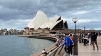 Warga berjalan di sepanjang Sydney Harbour dengan latar belakang pemandangan Sydney Opera House di Sydney pada 30 Desember 2017 (atas) dan pada 8 Maret 2020. (Saeed KHAN/AFP)