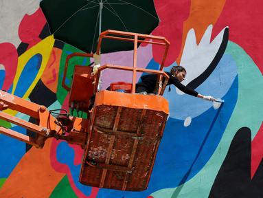 Seniman asal Brasil, Tarsila Schubert saat membuat mural di Museum Seni Terbuka, Kota Amman, Yordania, Kamis (29/9). Aksi melukis mural yang dilakukan Tarsila tersebut untuk mengampanyekan pentingnya pemberdayaan perempuan. (REUTERS/Muhammad Hamed)