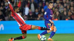 Aksi pemain Girona, Jonas Ramalho (kiri) menghalau bola sepakan pemain Barcelona, Philippe Coutinho pada La Liga Santander di Camp Nou stadium, Barcelona, (24/2/2018). Barcelona menang telak 6-1. (AFP/ Lluis Gene)