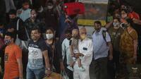 Penumpang yang mengenakan masker menunggu pemeriksaan tes COVID-19 di stasiun kereta jarak jauh di Mumbai, Maharashtra, Minggu (21/3/2021). India sedang menghadapi gelombang baru infeksi Covid-19 dan mencatat rekor lonjakan harian tertinggi dalam hampir empat bulan terakhir. (AP Photo/Rafiq Maqbool)