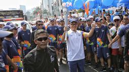 Dirut Bank Mandiri Kartika Wirjoatmodjo membawa obor saat prosesi Torch Relay Asian Games 2018 di Jakarta, Sabtu (18/8). Hari ini merupakan puncak kirab obor Asian Games 2018 dimana api abadi akan berlabuh di Gelora Bung Karno (Liputan6.com/Faizal Fanani)