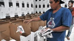 Pekerja memasukkan paket alat tulis untuk mencoblos ke dalam kotak suara Pemilu 2019 di Gudang Logistik KPU Kota Bekasi, Jawa Barat, Rabu (20/12). (Merdeka.com/Iqbal S. Nugroho)