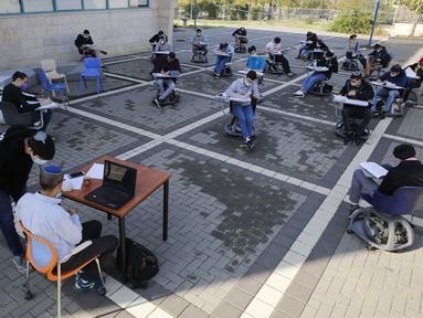 "Para murid sekolah menengah atas (SMA) belajar di area luar ruangan sebuah sekolah di Kota Modiin, Israel pada  29 November 2020. Israel memulai kembali kegiatan pembelajaran tatap muka untuk SMA di kota besar dan kecil yang dikategorikan sebagai zona ""hijau"" atau ""kuning"". (Xinhua/Gil Cohen Magen)"