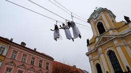 Sejumlah wanita berpakaian seperti malaikat melambakaikan tangan kearah pengunjung saat berayun di acara pasar Natal di kota Ustek, Republik Ceko (17/12). (Reuters/David W Cerny)