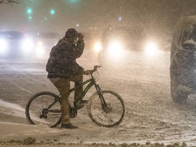 Pesepeda menunggu untuk menyeberangi jalan di tengah badai musim dingin di pusat kota Chicago, AS, 29 Desember 2020. Para komuter pagi di Chicago menghadapi jalanan yang licin dan lalu lintas yang lambat pada Rabu (30/12) saat badai musim dingin besar pertama melanda kota itu. (Xinhua/Joel Lerner)