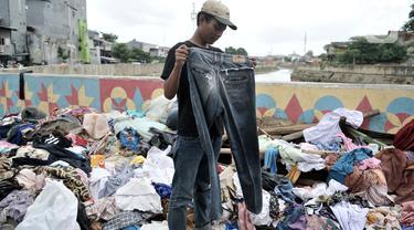 Warga korban banjir saat memilih pakaian sumbangan yang ditempatkan di pinggir Kali Ciliwung, Kampung Pulo, Jakarta Timur, Senin (6/1/2020). Banjir menyebabkan ratusan warga di Kampung Pulo kehilangan pakaian akibat rusak dan hanyut. (merdeka.com/Iqbal S. Nugroho)