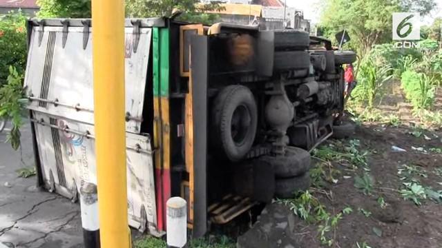 Diduga karena mengantuk, sopir truk box menabrak papan reklame dan perkarangan rumah warga.
